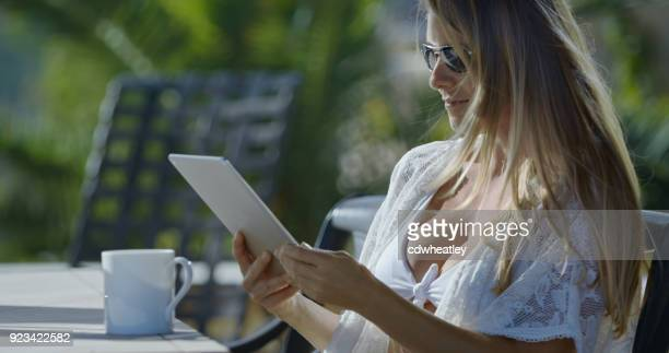 blonde woman drinking coffee and reading tablet at a luxury villa on tropical island