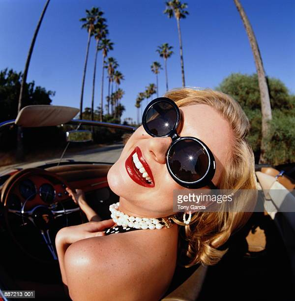 blonde woman driving in convertible car wearing sunglasses (wide angle - rich garcia stock-fotos und bilder
