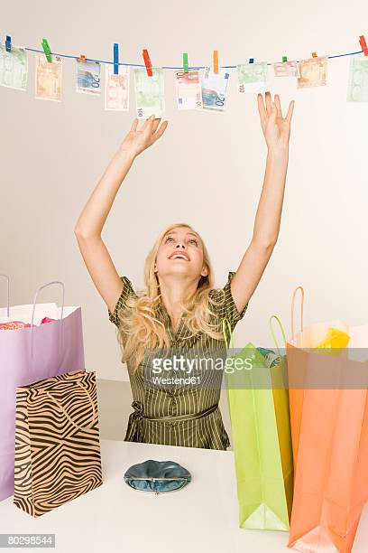 Young woman with shopping bags drying money on clothesline