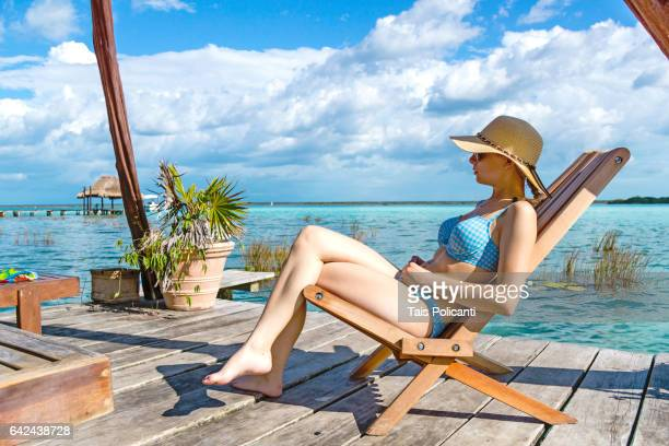 blonde woman enjoying at a floating terrace in the lagoon of bacalar, caribbean, mexico's mayan riviera, quintana roo, mexico - bikini bottom stock pictures, royalty-free photos & images
