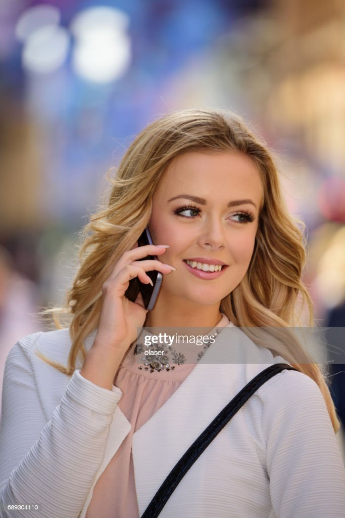 Blonde woman enjoying Stockholm spring, using mobile phone : Stock Photo