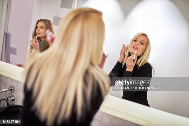 Blonde woman fixing makeup