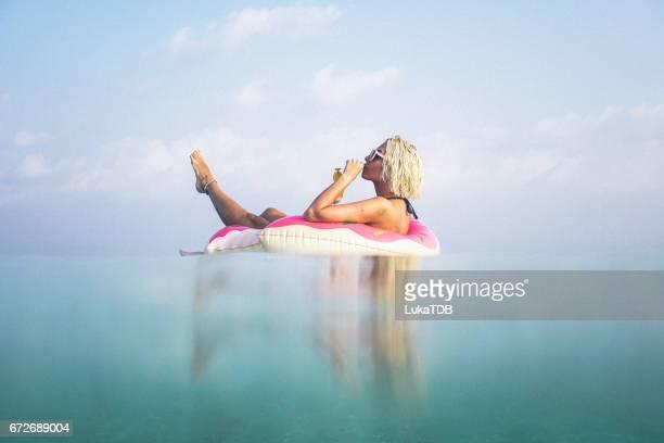 Femme blonde flottant dans l'océan, Maldives