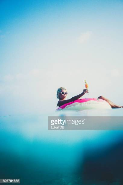 Blonde woman floating in the ocean, Maldives