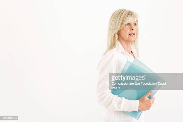 "blonde woman holding blue folders - ""compassionate eye"" stock-fotos und bilder"