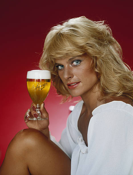 Blonde woman holding glass of beer against red background , portrait