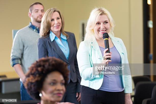 Blonde woman holding microphone asks question