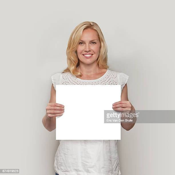 blonde woman holding white card - eric van den brulle stock pictures, royalty-free photos & images