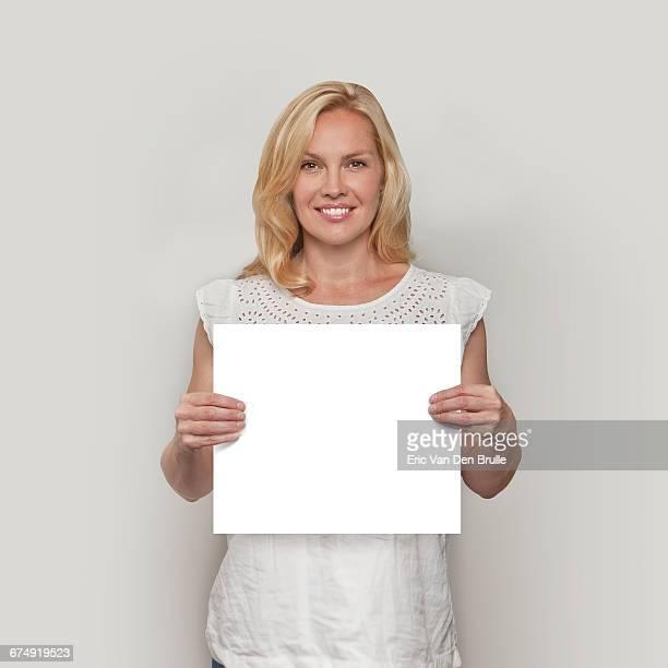 blonde woman holding white card - eric van den brulle photos et images de collection