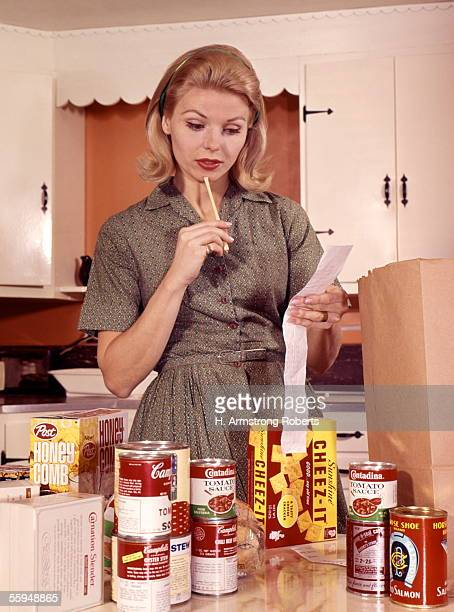 Blonde Woman Housewife In Kitchen Compare Cash Register Receipt To Items Groceries On Counter Brown Shopping Bag