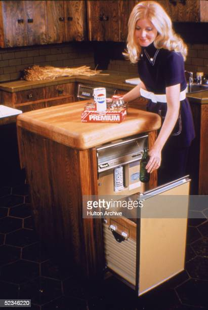 A blonde woman in a blue pantsuit with white stitching and belt places household food packaging in a Whirlpool brand trash compactor in a kitchen...