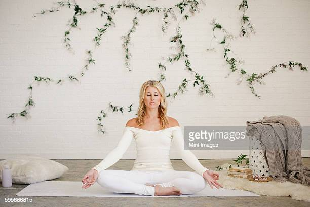 A blonde woman in a white leotard and leggings, sitting on a white mat in a room, doing yoga. A creeper plant on the wall behind her.