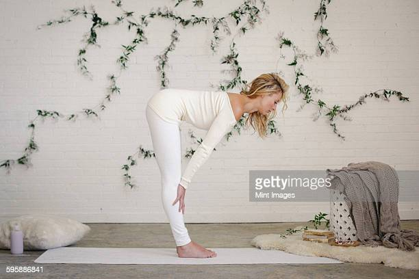 a blonde woman in a white leotard and leggings, standing on a white mat in a room, bending forwards. - beautiful women bent over stock photos and pictures