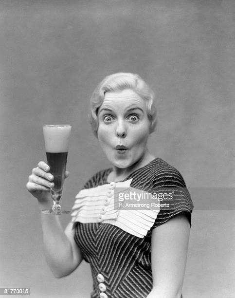 Blonde Woman In Black Dress With Stripes & White Buttons & Trim Holding A Pilsner Glass Of Beer With A Large Head With Pursed Lips & Poppy Eyes Cartoon.