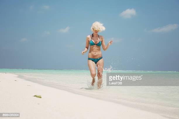 Blonde Frau im blauen Bikini laufen durch Meer auf den Malediven