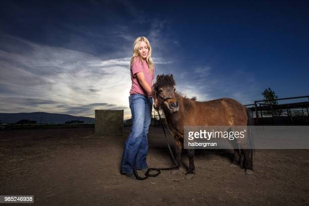 Blonde Woman in Stable Yard with Miniature Horse