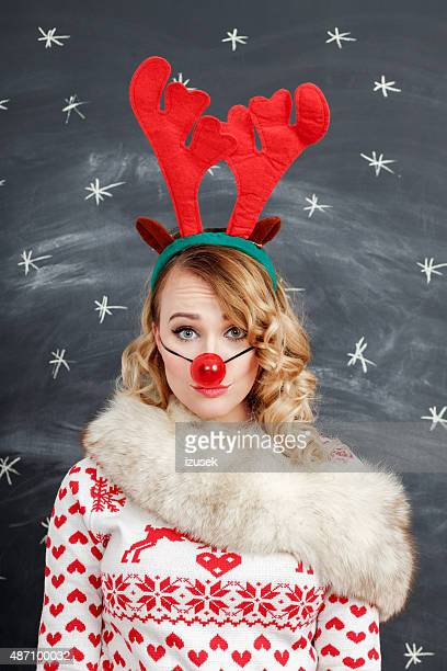 Blonde woman in winter outfit and reindeer antlers headband