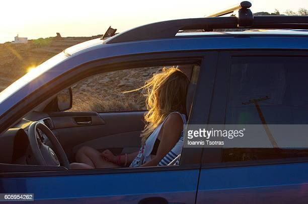 Blonde woman inside a blue car during sunset