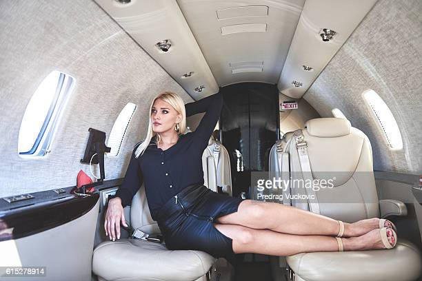 Blonde woman inside private jet aeroplane