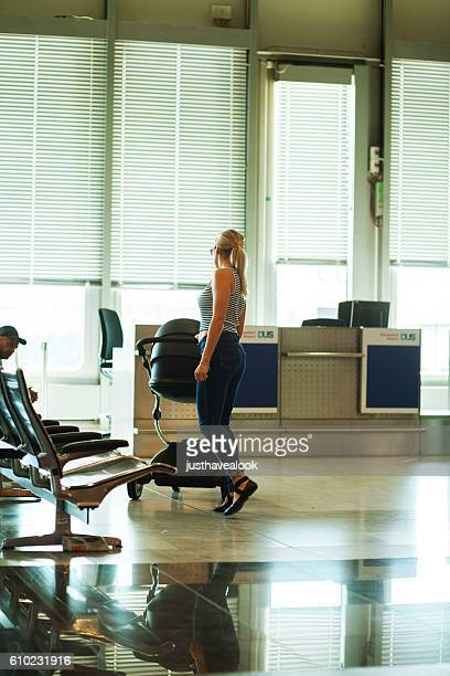 Blonde woman is dancing with baby buggy in airport