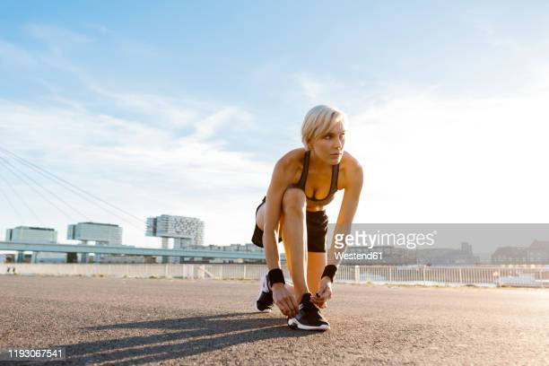 blonde woman jogging, tying shoes - cabelo curto comprimento de cabelo imagens e fotografias de stock