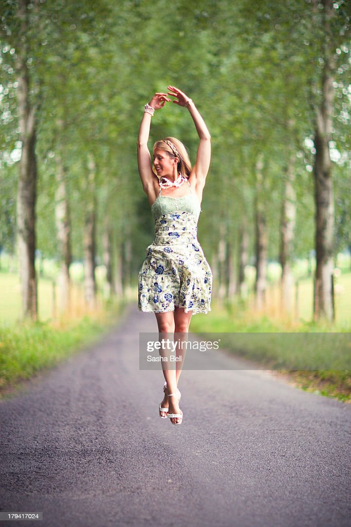 Blonde woman jumping in avenue : Stock Photo