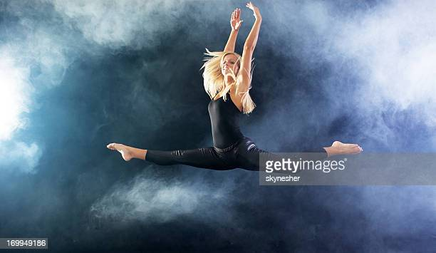 Blonde woman jumping through the fog.
