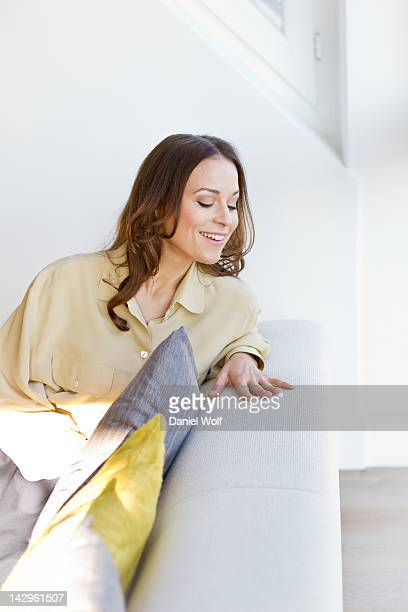 Blonde woman looking down from couch smiling