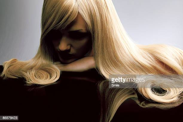 blonde woman looking down into dark reflection - straight hair stock pictures, royalty-free photos & images