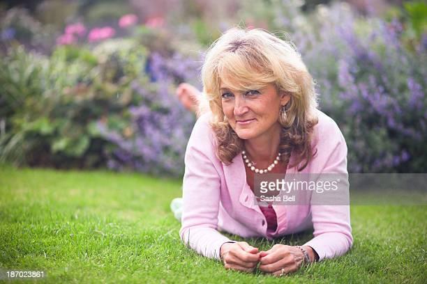 Blonde woman lying down on grass
