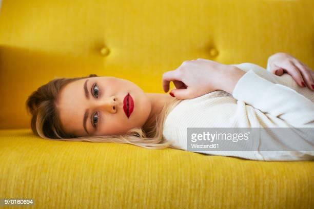 blonde woman lying on sofa - lying down imagens e fotografias de stock