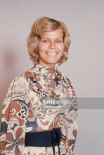 A blonde woman models a paisley print blouse with a wide belt c 1970