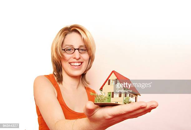 blonde woman offering a house - real_property stock pictures, royalty-free photos & images