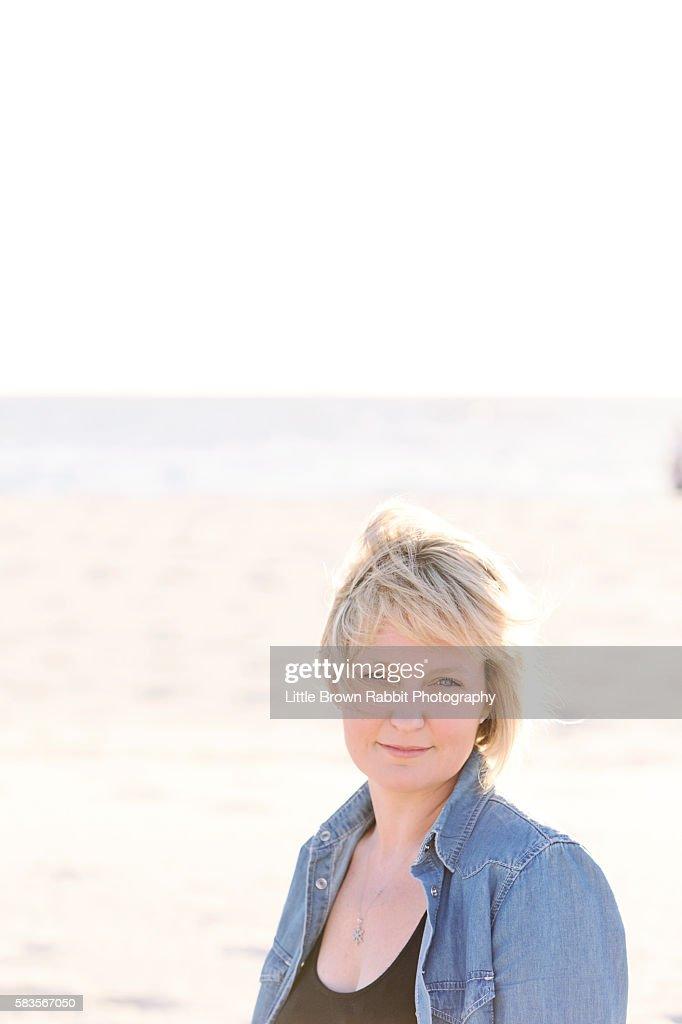 Blonde Woman on a Beach in a Denim Shirt : Stock Photo