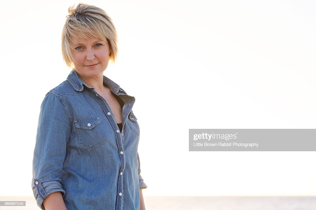 Blonde Woman on a Beach in a Denim Shirt : Stock Photo