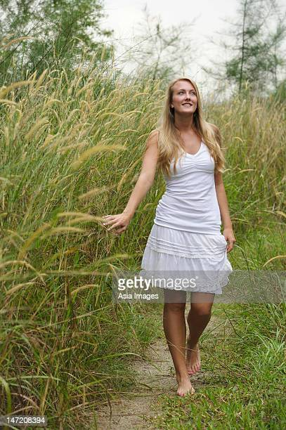 blonde woman on grassy path, hand on tall grass - tall blonde women stock photos and pictures