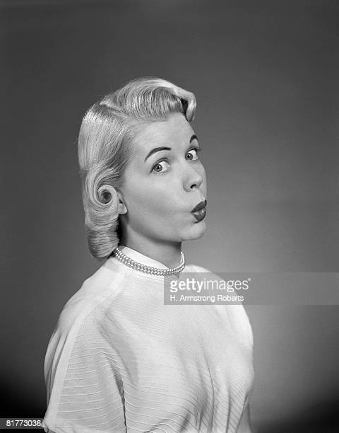 Blonde Woman Page Boy Hair Pearl Necklace White Blouse 3 4 Profile Look At Camera Lips Pursed Whistle Kiss Funny Face Expression.