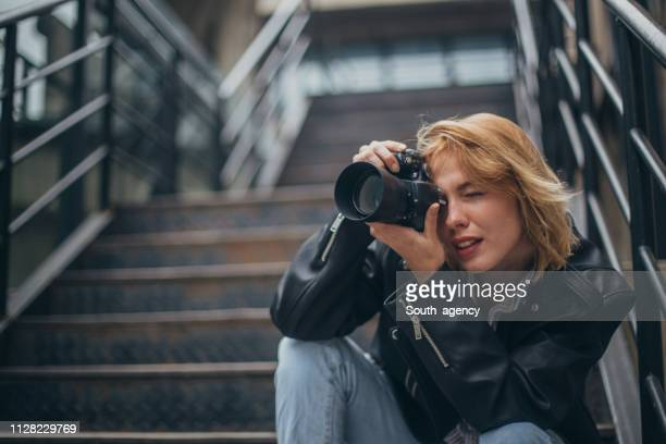 blonde woman photographer sitting on steps in city - photographer stock pictures, royalty-free photos & images