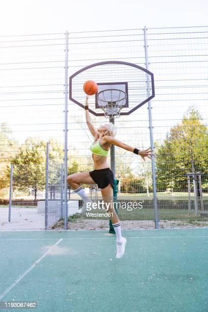 blonde woman playing basketball, dunking - バスケットボールのシュート ストックフォトと画像