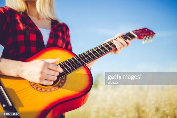 Blonde woman playing guitar in wheat field and enjoying in free time