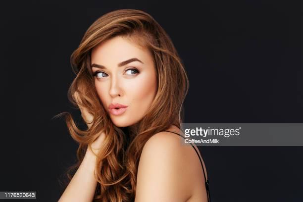femme blonde posant sur le fond noir - jolie brune femmes yeux bleus photos et images de collection