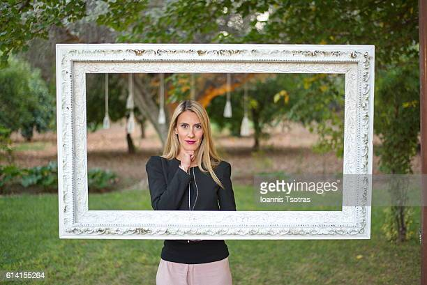 Blonde woman posing inside a picture frame