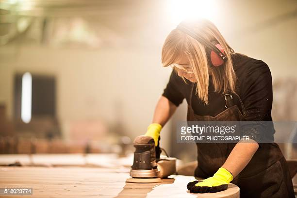 Blonde woman power sanding wooden furniture