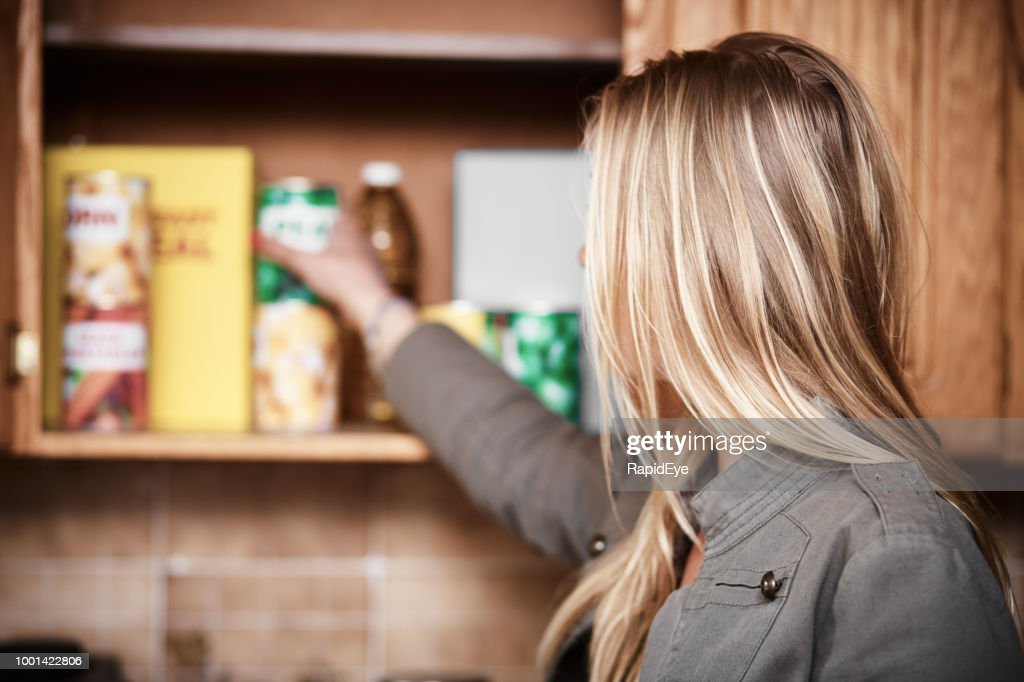 Blonde woman reaching into kitchen cupboard for canned food. : Stock Photo