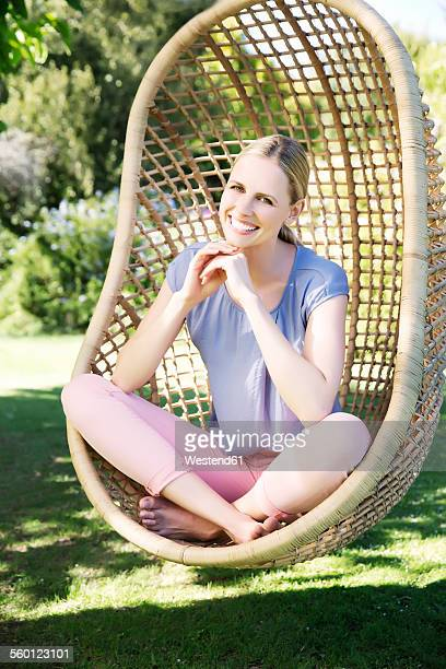 blonde woman relaxing in hanging chair - mid adult women stock pictures, royalty-free photos & images