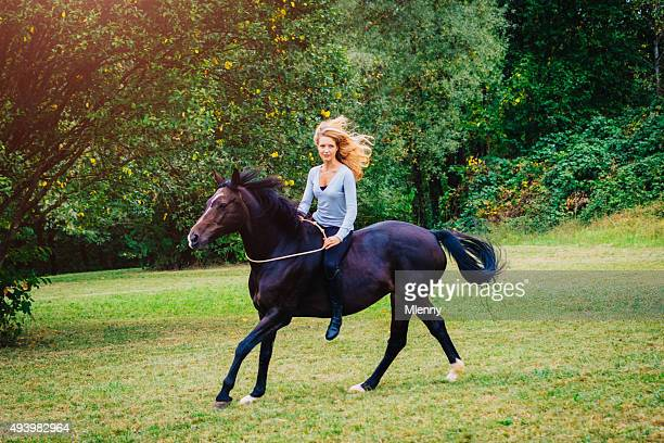 Blonde woman riding canter with black horse outdoors