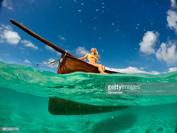Blonde woman seen from underwater sitting on a wooden boat