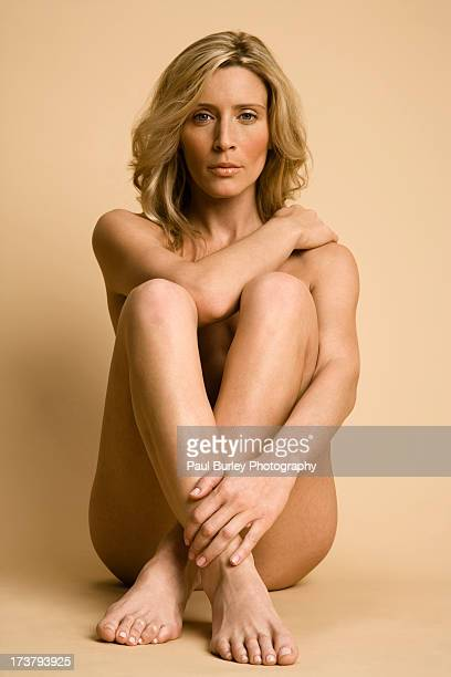 Blonde woman sitting naked.
