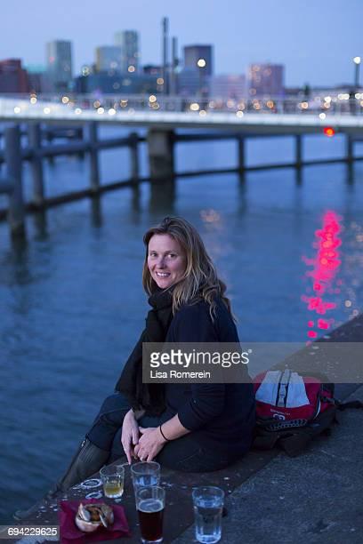 Blonde woman sitting on a riverbank