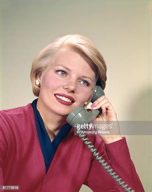 Blonde woman smiling and talking on telephone.